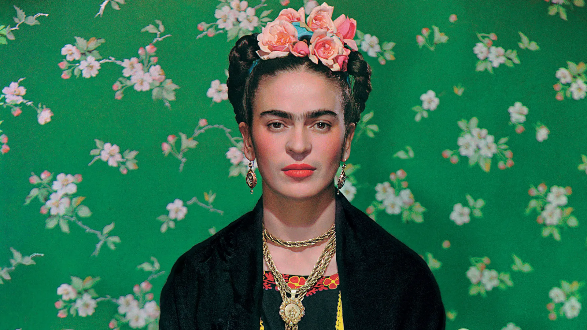 Frida Kahlo wearing luscious red lipstick, flowers in her hair, gold necklaces and long earrings, against a floral green background.