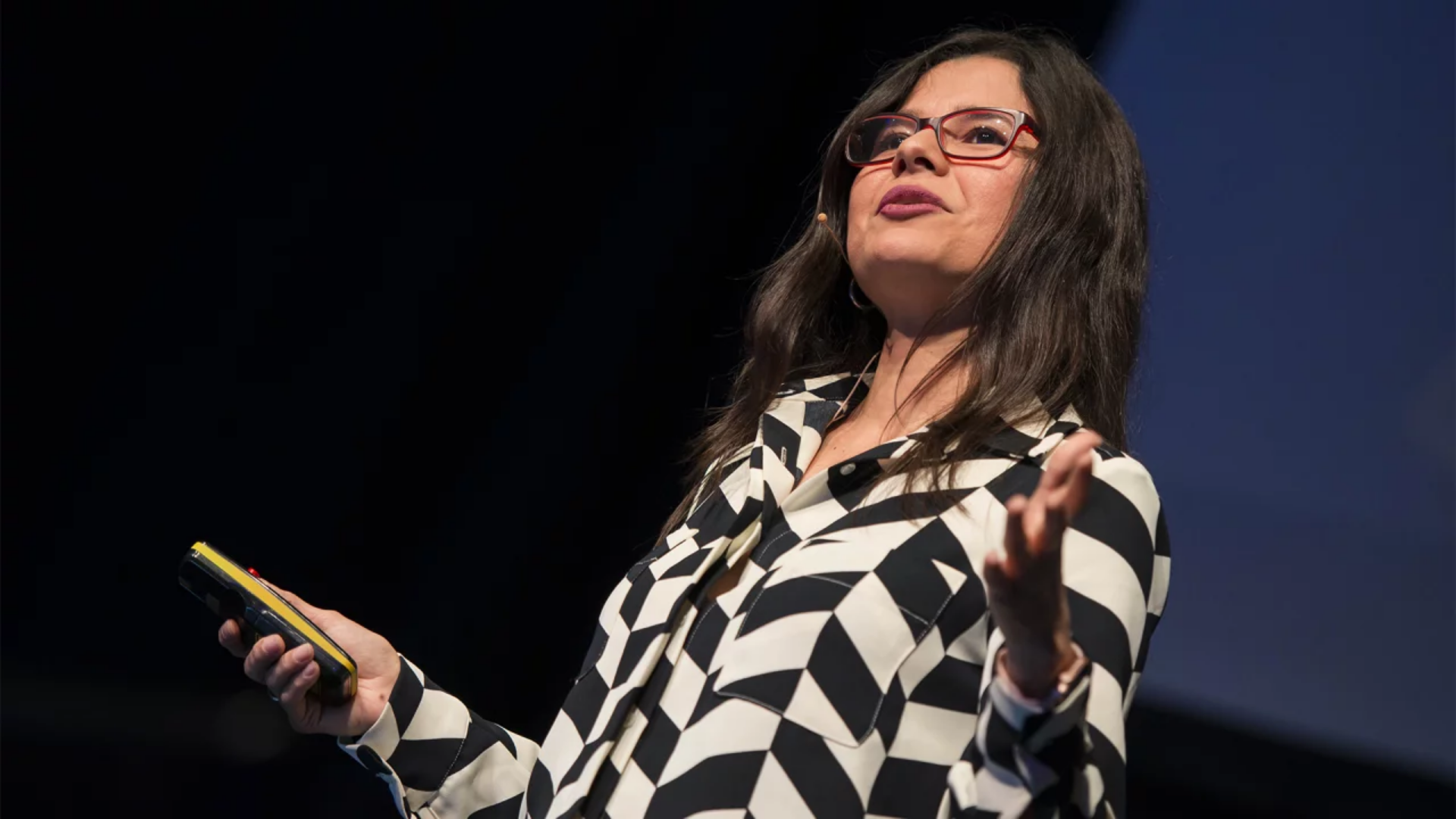 Aleyda Solís, wearing a black and white striped shirt and red framed glasses, standing on a stage doing a talk.