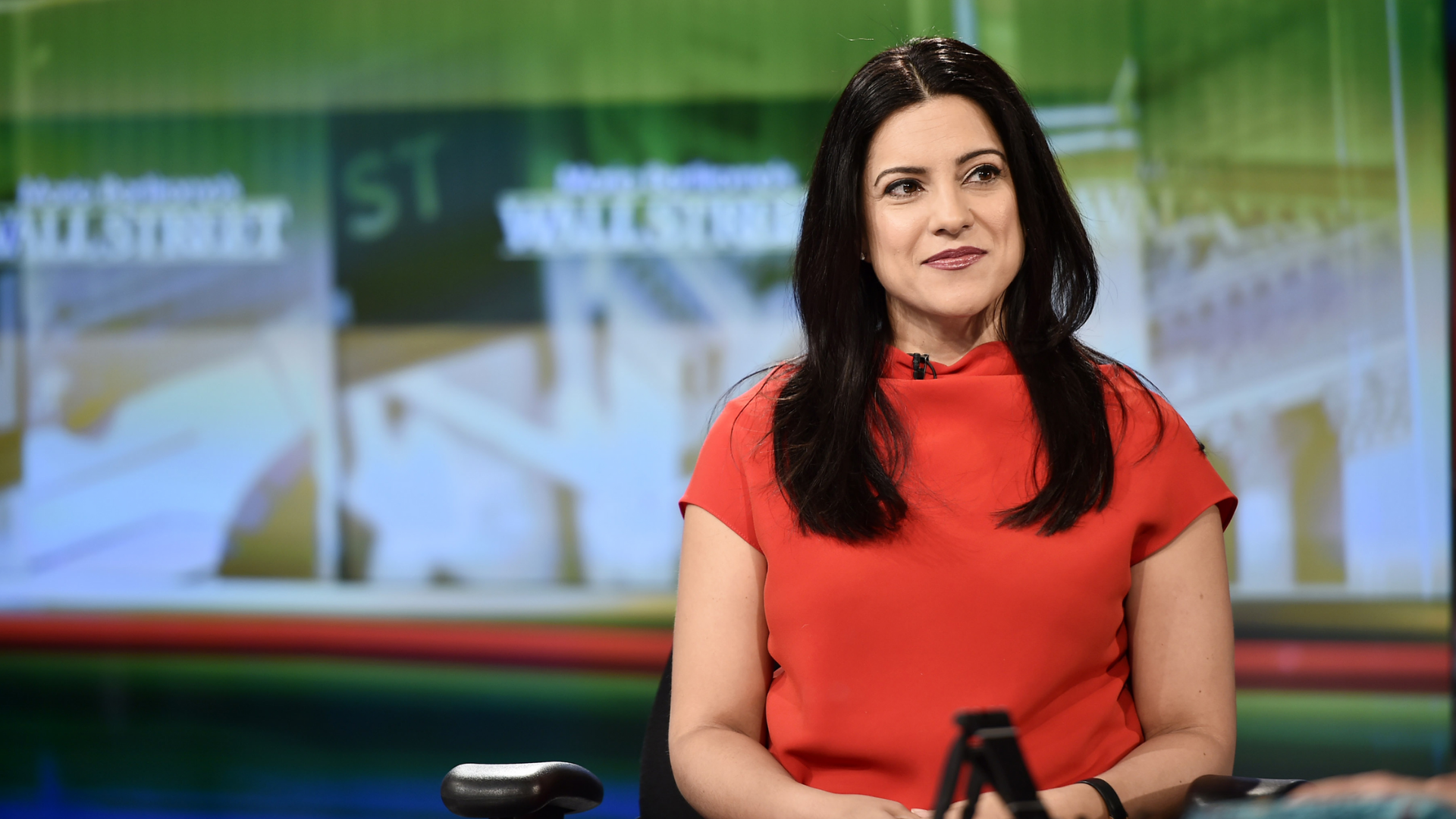 Reshma Saujani on a news show, wearing a red, short sleeved top, with long brown hair. There is a green news screen in the background.