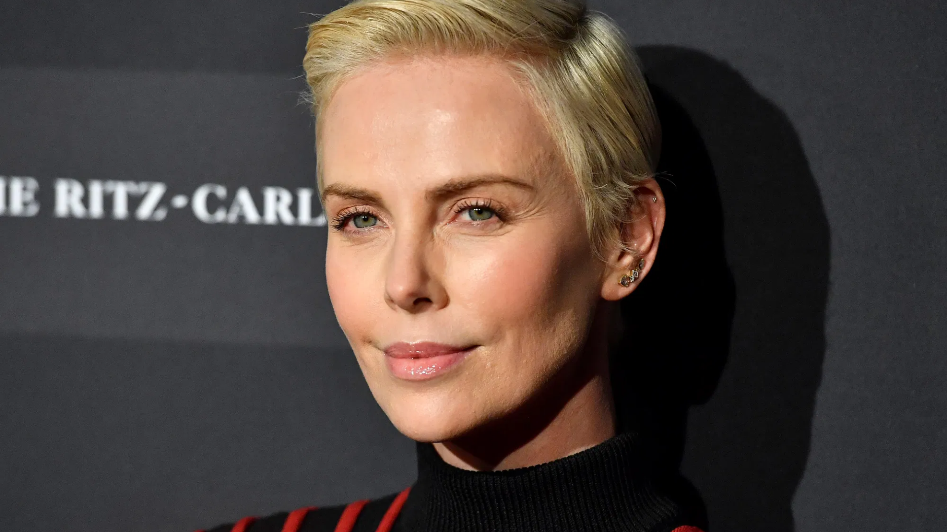 Charlize Theron on the red carpet, with a short blonde hair - wearing stripy black and red turtleneck jumper and stud earrings.