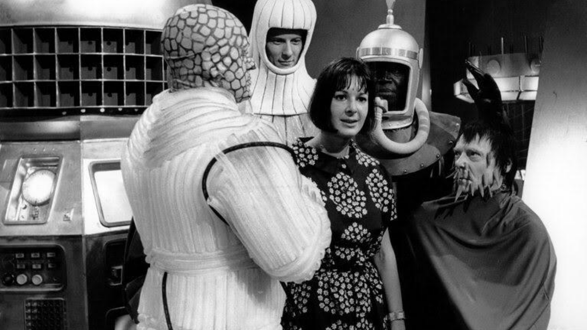 Verity Lambert, pictured on a sci-fi television set, with three actors around her, dressed as a variety of aliens.