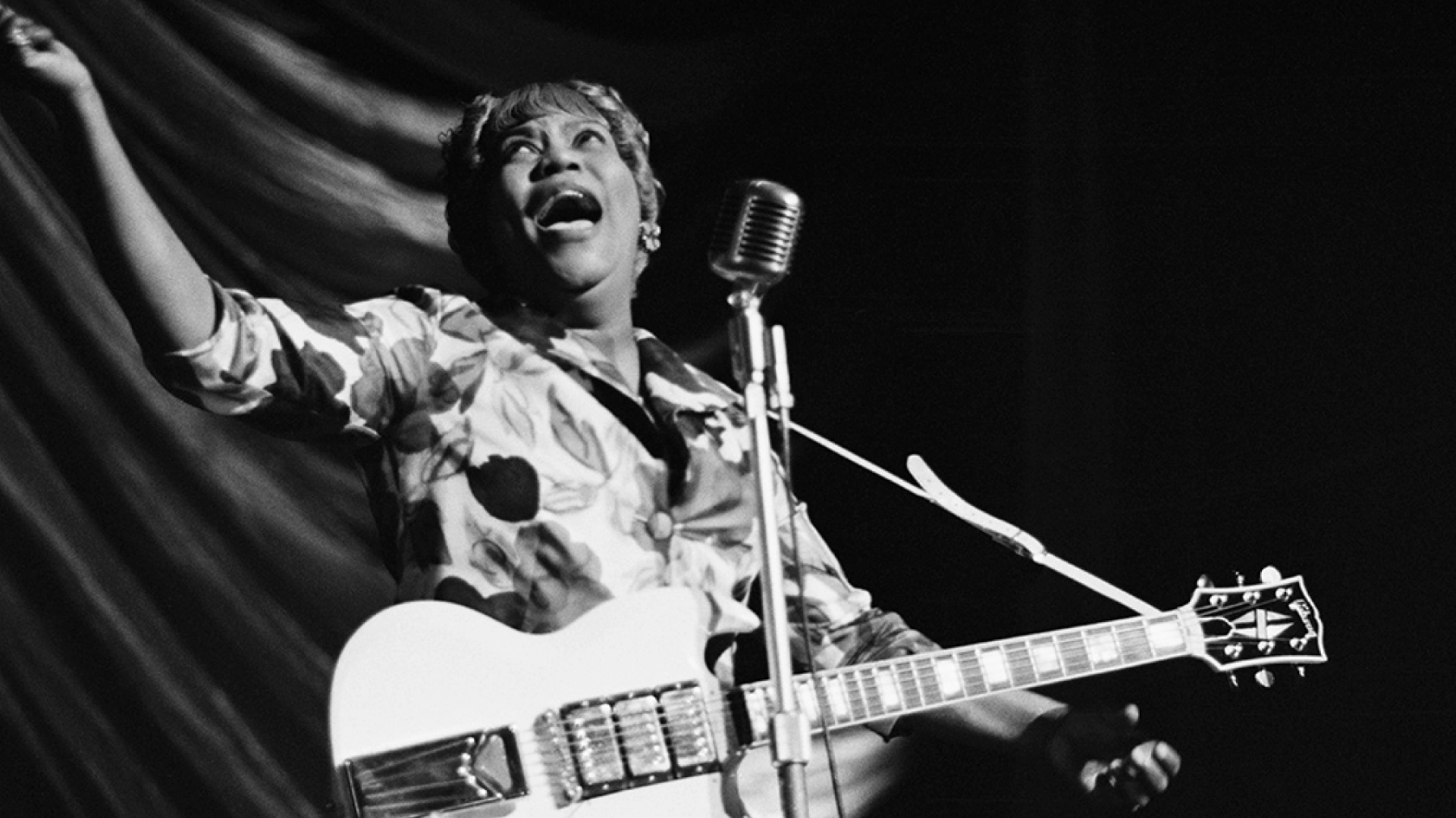 Old black and white photo of Sister Rosetta Tharpe, on stage with a guitar, singing into a microphone.