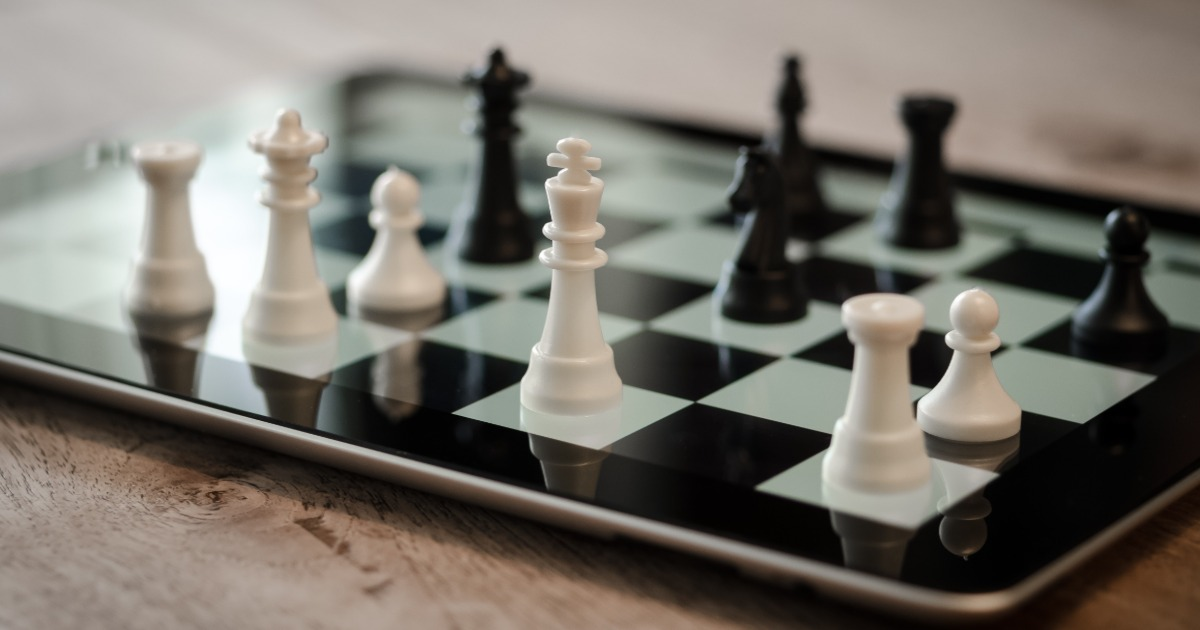 Real chess pieces on a virtual tablet screen chess board